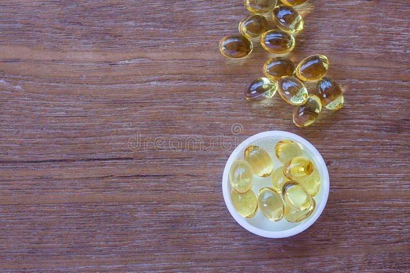 Ômega 3 cápsulas do óleo do fígado de peixes no fundo de madeira imagem de stock