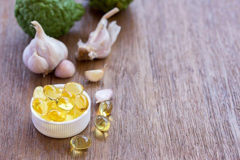 Ômega 3 cápsulas e alho do óleo do fígado de peixes no fundo branco imagem de stock