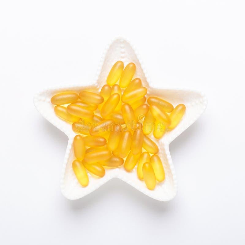 Ômega 3 cápsulas na placa da forma da estrela na vitamina amarela branca D dos softgels do óleo de peixes do fundo, E, um supleme foto de stock royalty free