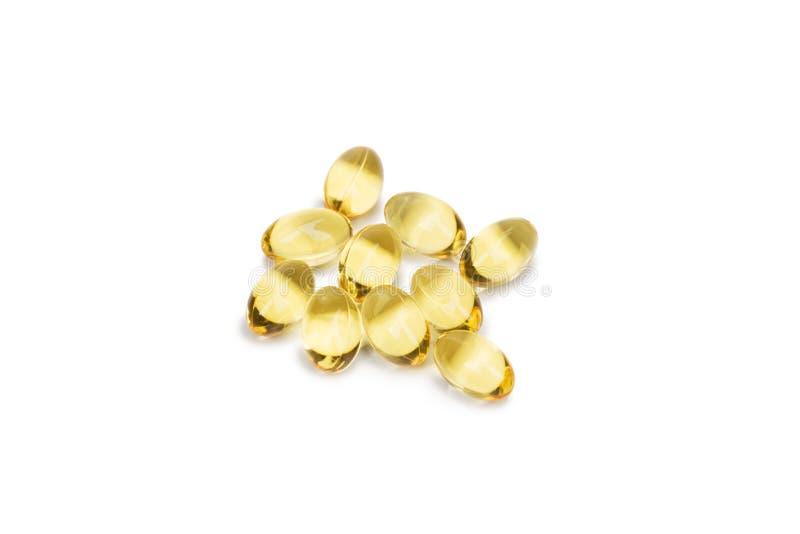 Ômega do óleo de fígado de bacalhau 3 cápsulas ou pils do gel isoladas em um fundo branco Um grupo de tabuletas transparentes do  imagens de stock