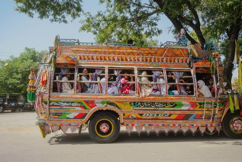 Ônibus decorado colorido com homens e os passageiros paquistaneses das mulheres fotos de stock