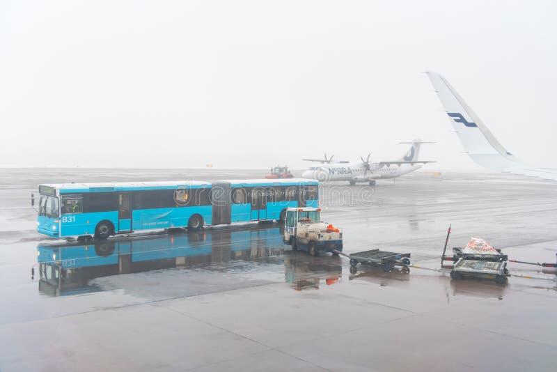 Ônibus do aeroporto do estacionamento do aeroporto de Helsínquia para o passageiro da picareta acima do franco imagens de stock royalty free