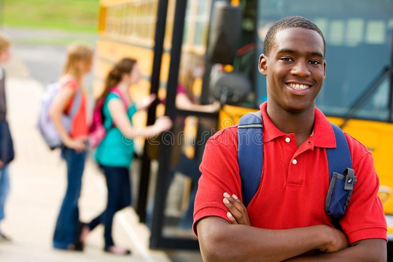 Ônibus escolar: Estudante adolescente com ônibus escolar atrás foto de stock royalty free