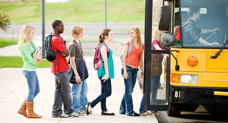 Ônibus escolar: Linha de estudantes que embarcam o ônibus imagens de stock royalty free