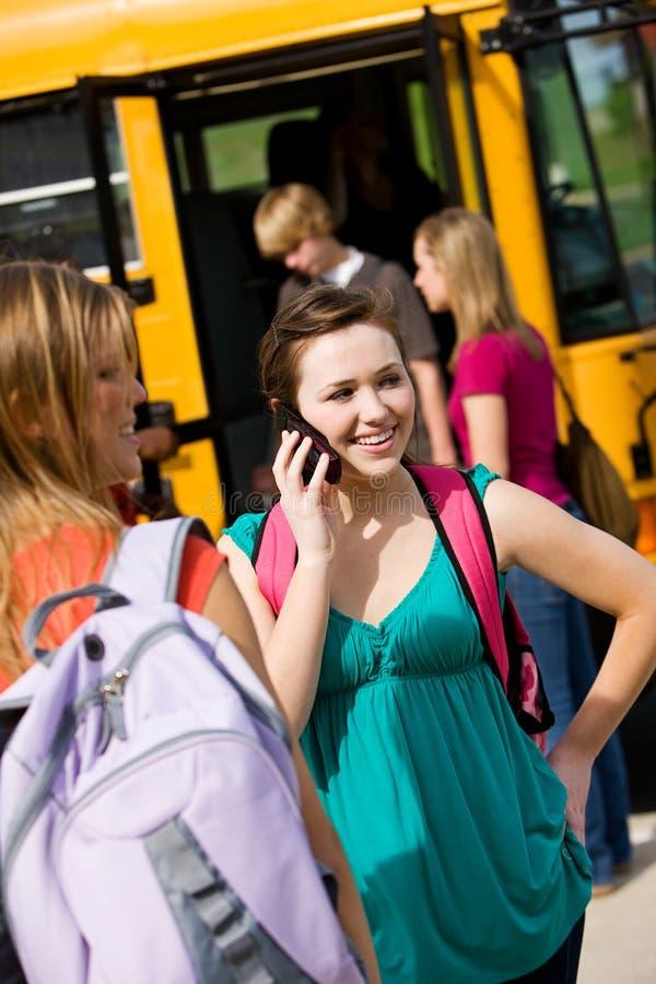 Ônibus escolar: A menina chama o amigo antes de embarcar o ônibus imagens de stock royalty free