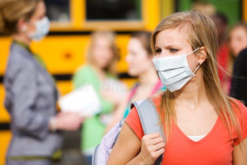 Ônibus escolar: A menina tem que vestir a máscara para evitar a doença imagens de stock