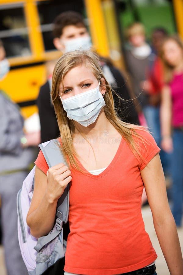 Ônibus escolar: Vestindo uma máscara para evitar a gripe foto de stock