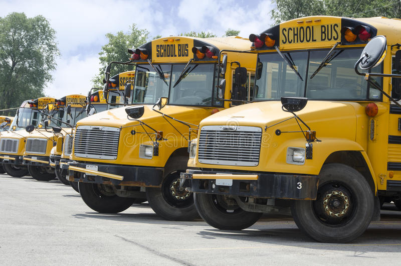 Ônibus escolares alinhados para transportar crianças imagens de stock royalty free