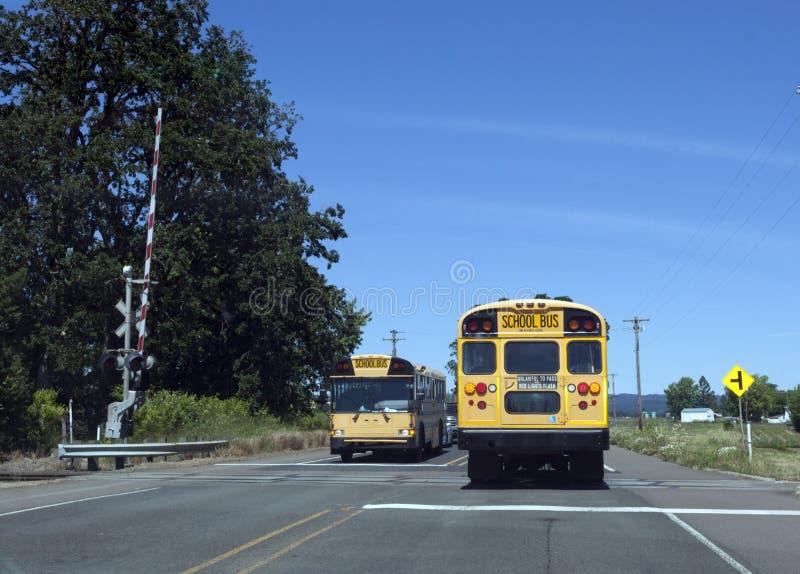 Ônibus escolares no cruzamento de estrada de ferro fotografia de stock
