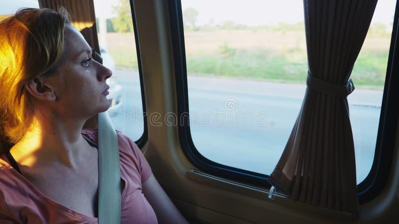 Ônibus pensativo triste da equitação da menina e vista para fora da janela fotografia de stock