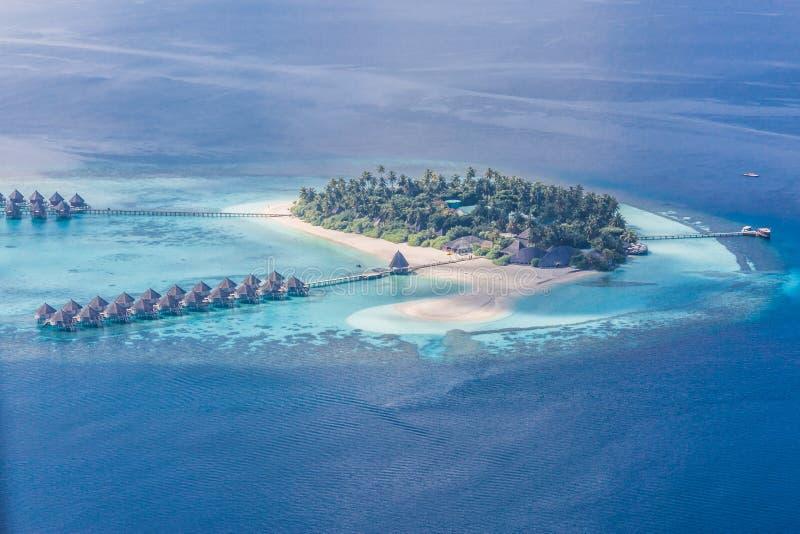 Ö för lyxig semesterort i Maldiverna med vattenbungalowbakgrund och flyg- sikt för blå havshimmel arkivbilder