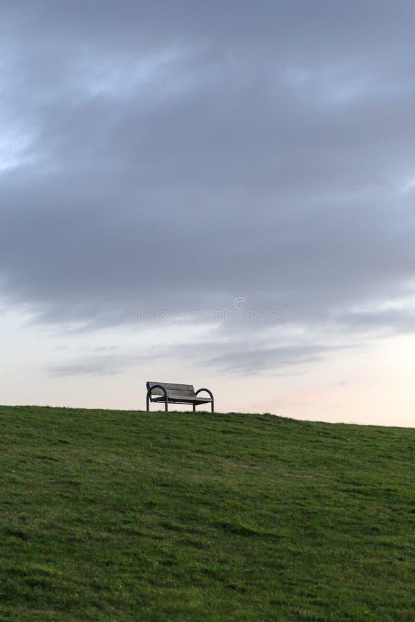 Öde bänk framme av en mörk himmel på en fördämning på Nordsjön arkivbild