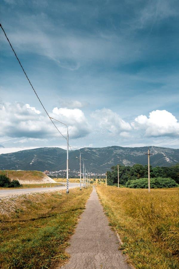 Öde promenad längs en Asphalt Road Overlooking The Mountai royaltyfri bild