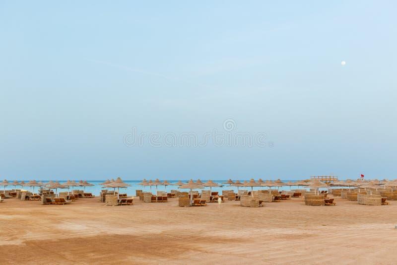 Öde strand med schäslonger i aftonen royaltyfri bild