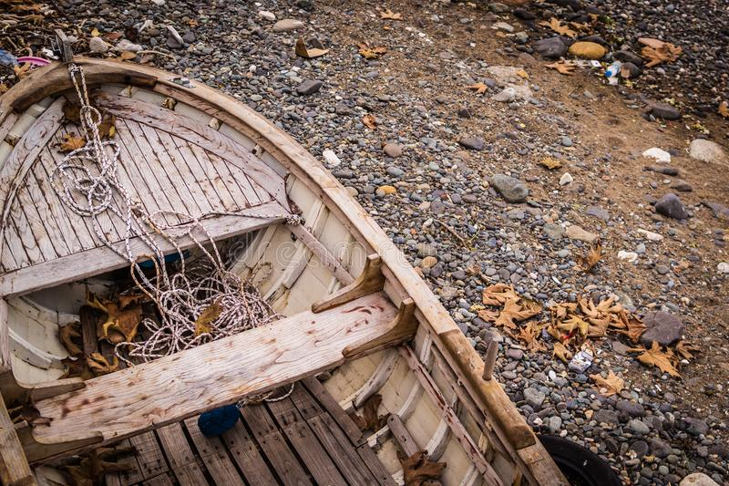 Ödelagd roddbåt på kusten arkivfoto