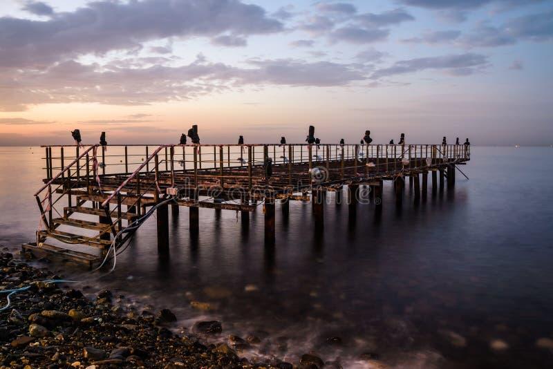 Ödelagd skeppsdocka på solnedgång med det lugna havet arkivbilder