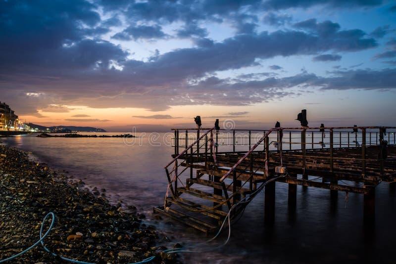 Ödelagd skeppsdocka på solnedgång med det lugna havet royaltyfria bilder