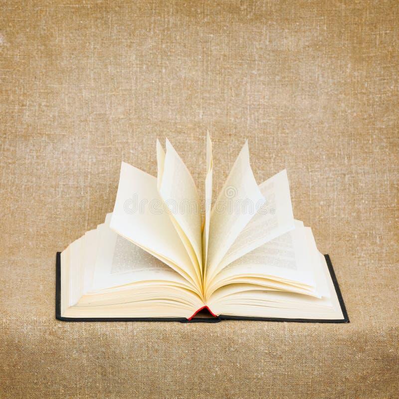 Öffnen Sie altes Buch auf braunem Segeltuchhintergrund lizenzfreie stockbilder