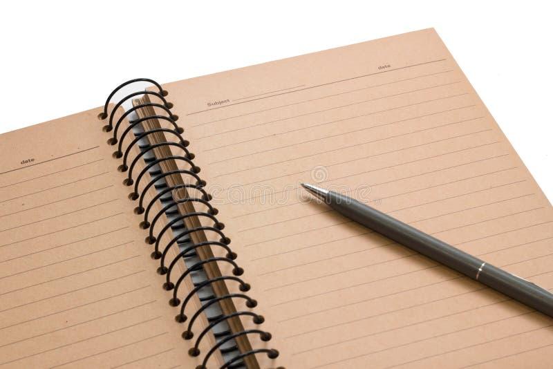 Öffnen Sie braunes Anmerkungsbuch mit gezeichnetem und grauem Stift auf weißem Hintergrund stockfotos
