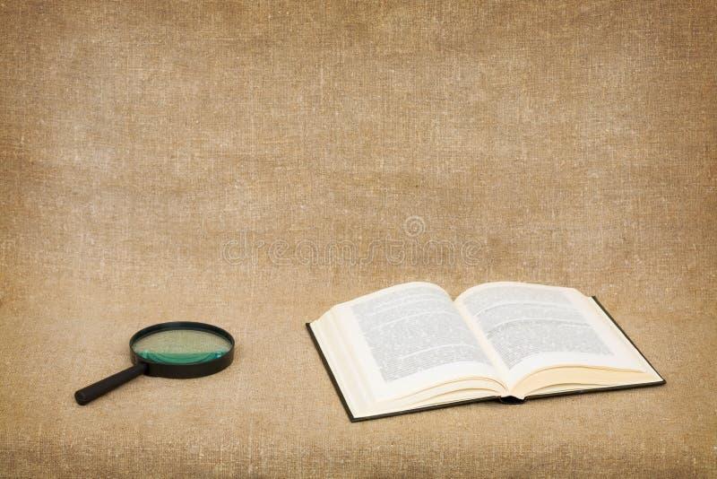 Öffnen Sie Buch und Vergrößerungsglas auf Segeltuch stockfotografie