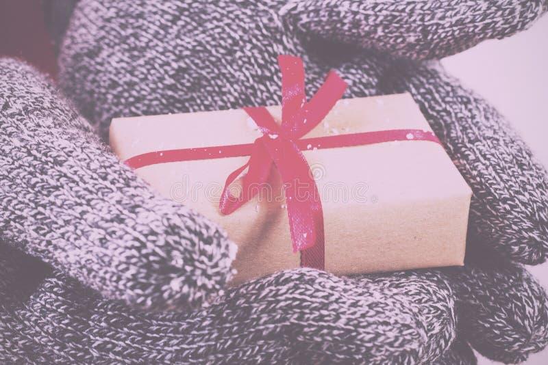 Öffnen Sie die Hände, die ein Geschenk eingewickelt mit einer roten Band Weinlese R halten stockbilder