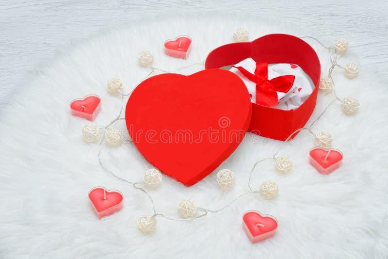 Öffnen Sie Geschenkbox in Form des Herzens Unterwäsche, Kerzen und garl lizenzfreies stockbild