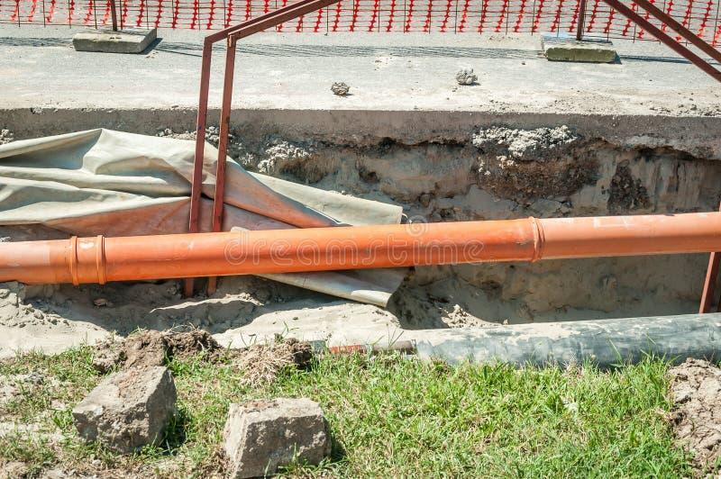 Öffnen Sie Graben auf dem Straßenaushöhlungsstandort mit sichtbaren Rohren für Wassergas- und Fernheizungsrohrleitungssystem in d lizenzfreie stockfotos