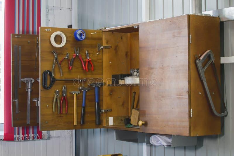 Öffnen Sie hölzernen Schrank mit Arbeitsgeräten lizenzfreie stockbilder