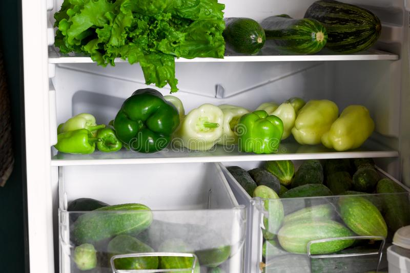 öffnen Sie Kühlschrankregale und -fächer voll des grünen Gemüses lizenzfreie stockbilder