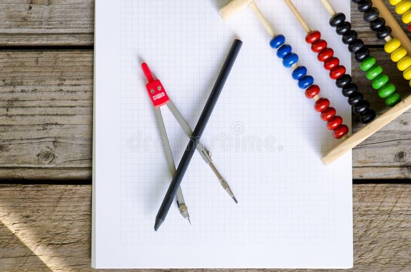 Öffnen Sie Mathenotizbuch mit farbigen Zählungsabakus und Stahl compas stockfotos