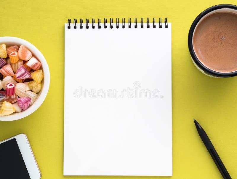 Öffnen Sie Notizblock auf Spirale mit sauberer weißer Seite, Schale mit Kakao, Karamelen in einer Schüssel, Smartphone und Bleist stockfotos