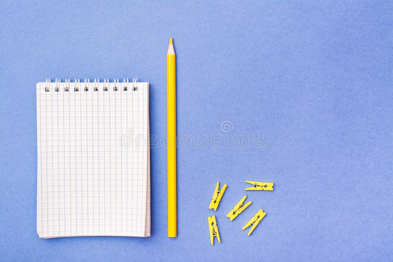 Öffnen Sie Notizblock in einem Käfig auf einer Spirale, einem gelben Bleistift und Klammern lizenzfreies stockfoto