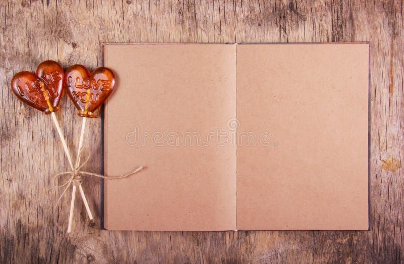 Öffnen Sie Notizbuch mit Leerseiten und Lutscher zwei in Form eines Herzens lizenzfreie stockfotografie