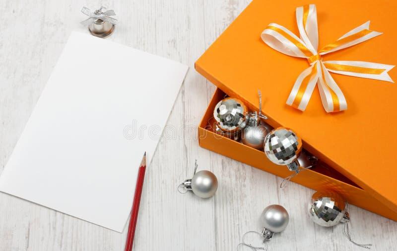 Öffnen Sie orange Geschenkkasten mit silbernem Weihnachtsflitter lizenzfreie stockbilder