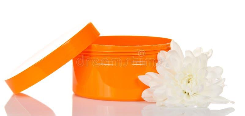 Öffnen Sie orange Glas mit Gesichtscreme und -blume lizenzfreies stockfoto