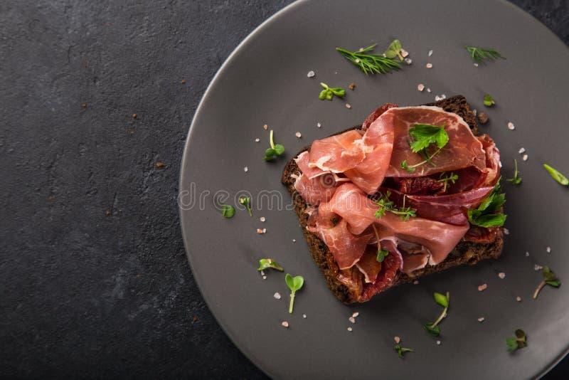 Öffnen Sie sanwiches mit dunklem Roggenbrot, Prosciutto und sonnengetrocknetem Tom lizenzfreie stockfotografie