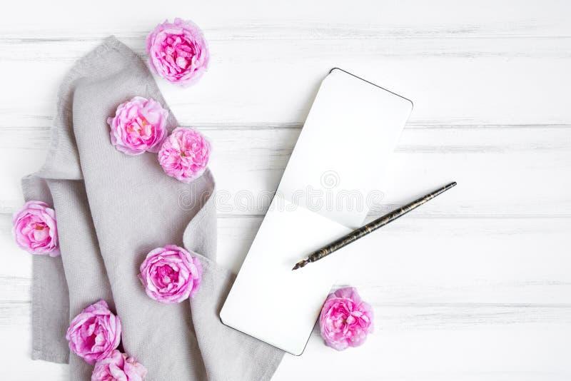 Öffnen Sie Sketchbook, schöne rosa Rosen auf grauer Leinengewebetischdecke Zusammensetzung auf weißem Weinleseholztisch Flache La lizenzfreie stockfotografie