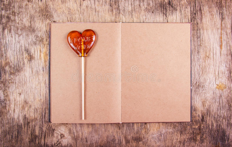 Öffnen Sie Tagebuch mit leeren Seiten Schatz auf einem Stock Lutscher in Form des Herzens stockfotografie