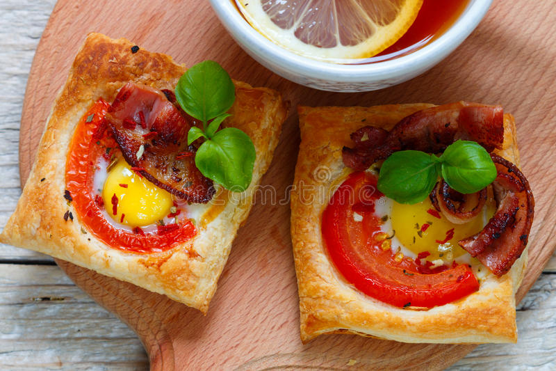 Öffnen Sie Torten des Blätterteiges mit Wachtelei, Tomaten, Speck und Basilikum Frühstück lizenzfreie stockfotografie
