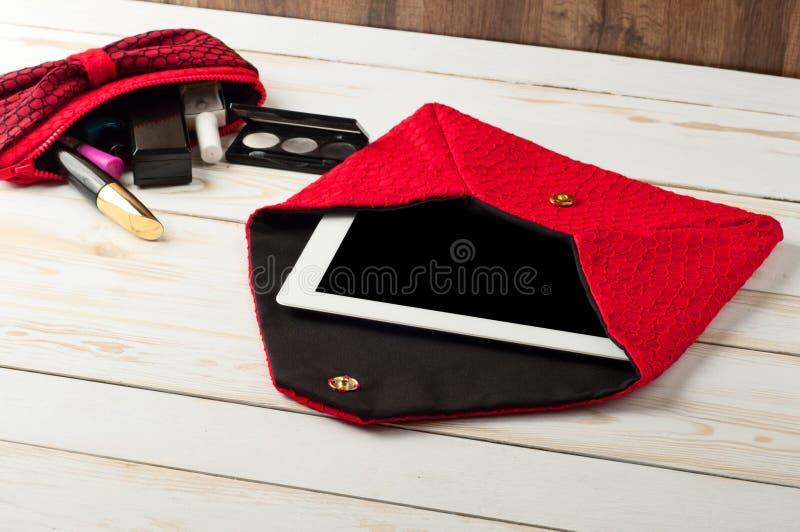 Öffnen Sie weibliche Handtasche des roten Stiftes mit Tablet-Computer in einem weißen Holz lizenzfreie stockbilder