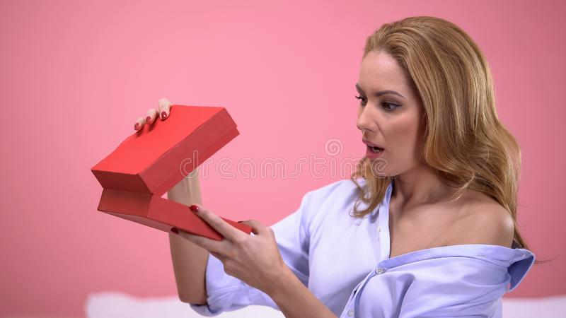 Öffnende Geschenkbox aufgeregter Dame mit wünschenswertem Geschenk von geliebtem, Überraschung stockfoto