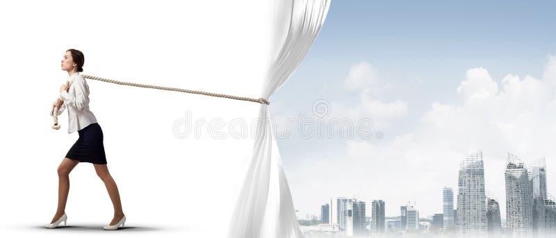 Öffnender weißer Vorhang der jungen Frau und Darstellen der modernen Stadtlandschaft stockbild