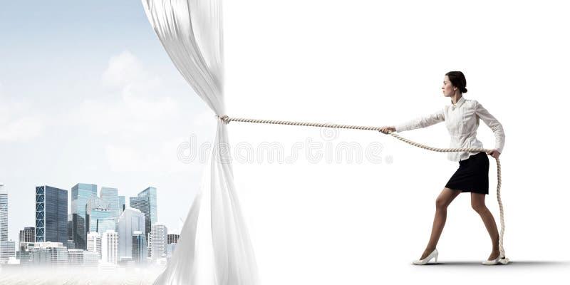 Öffnender weißer Vorhang der jungen Frau und Darstellen der modernen Stadtlandschaft lizenzfreie stockfotos
