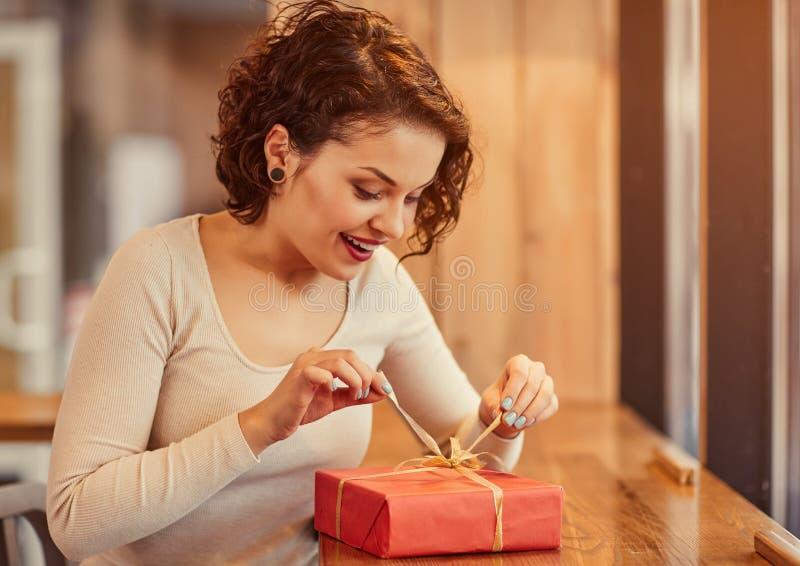 Öffnendes Geschenk der angenehmen Frau lizenzfreie stockfotografie
