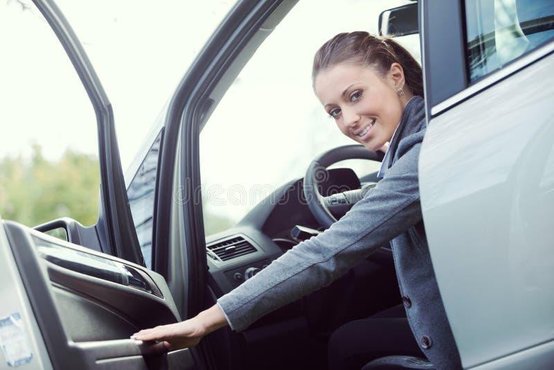 Öffnungs-Autotür der jungen Frau stockfotografie