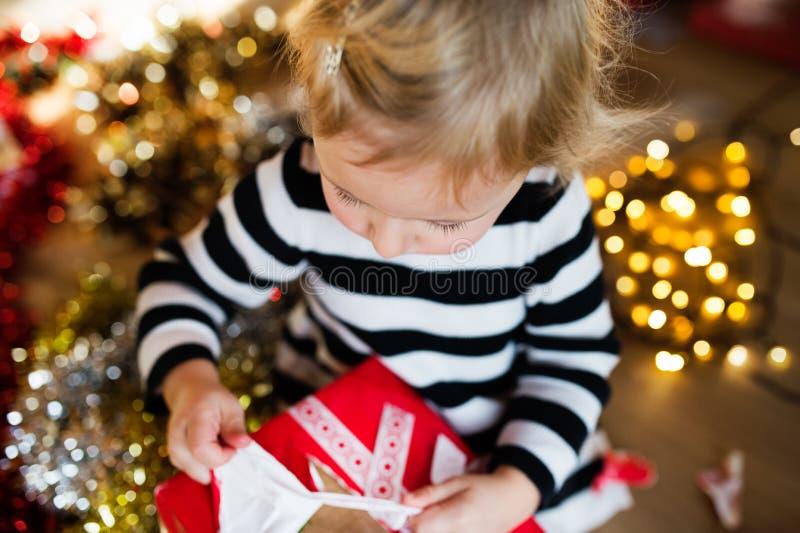 Öffnungs-Weihnachtsgeschenk des kleinen Mädchens stockfotografie