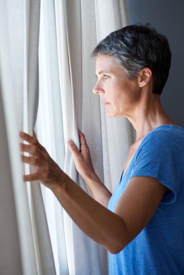 Öffnungsvorhänge der älteren Frau und Fenster heraus schauen lizenzfreies stockbild