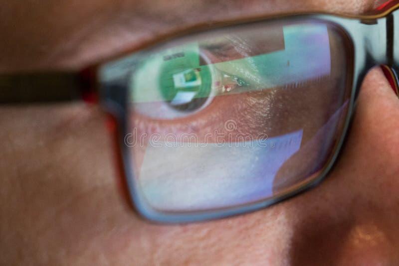 Ögat för Closeupman` s i exponeringsglas arbetar på bärbara datorn på natten royaltyfria bilder