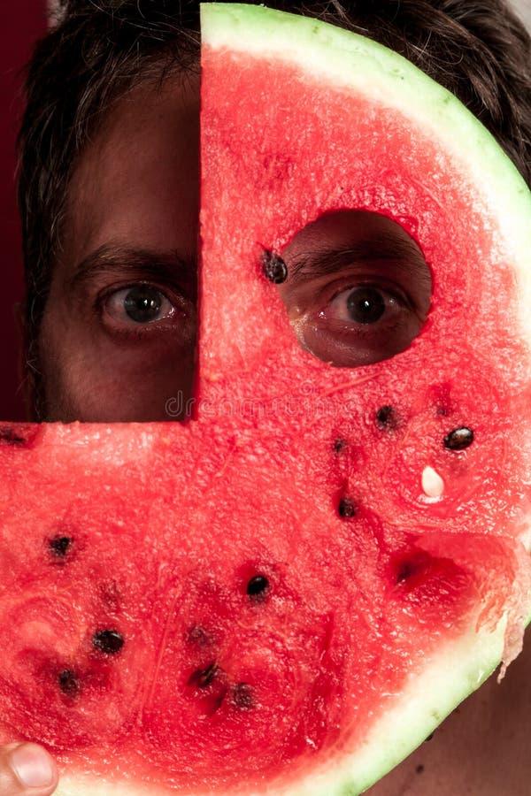 Ögon av mannen till och med skiva av den röda vattenmelon royaltyfria bilder