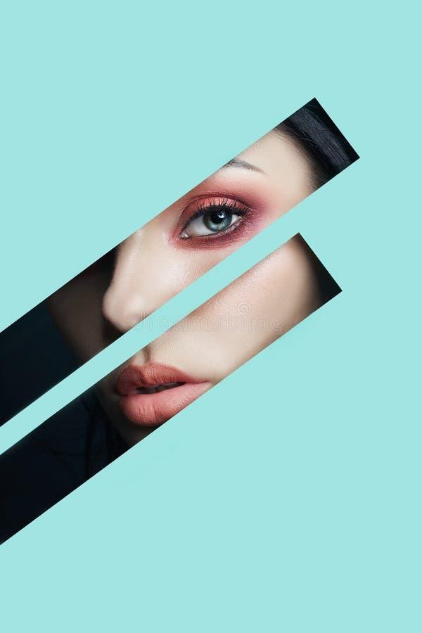 Ögon för makeup för skönhetframsida röda av en ung flicka i ett skuret upp hål av blått papper Kvinna med röd glödande skugga för royaltyfria bilder